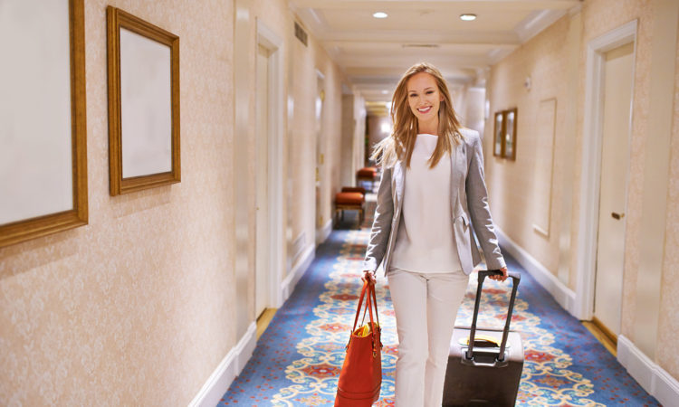 A beautiful woman standing in a hotel with her luggage